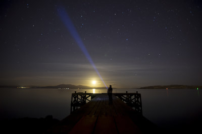 Self portrait on Portencross jetty at night, pointing a torch at the stars.