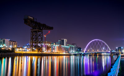 The lights of Glasgow reflected in the Clyde with the Finnieston crane and squinty bridge.